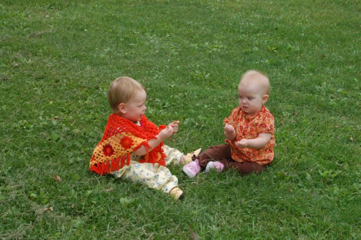 Brigid and Madeline play.  Madeline stole Brigid's poncho -